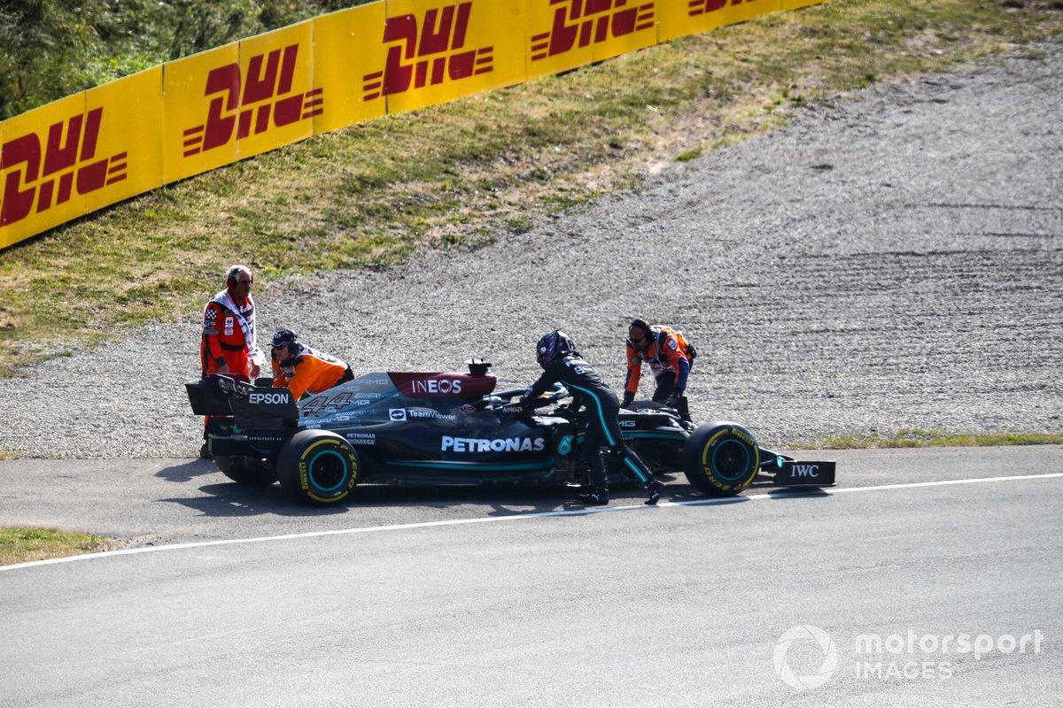 Los oficiales de pista asisten a Lewis Hamilton, de Mercedes, tras una avería en la FP2