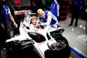 Nikita Mazepin, Haas F1, toont de cockpit van zijn auto aan een jonge gast