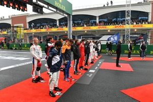 The drivers line up on the grid for the national anthem prior to the start