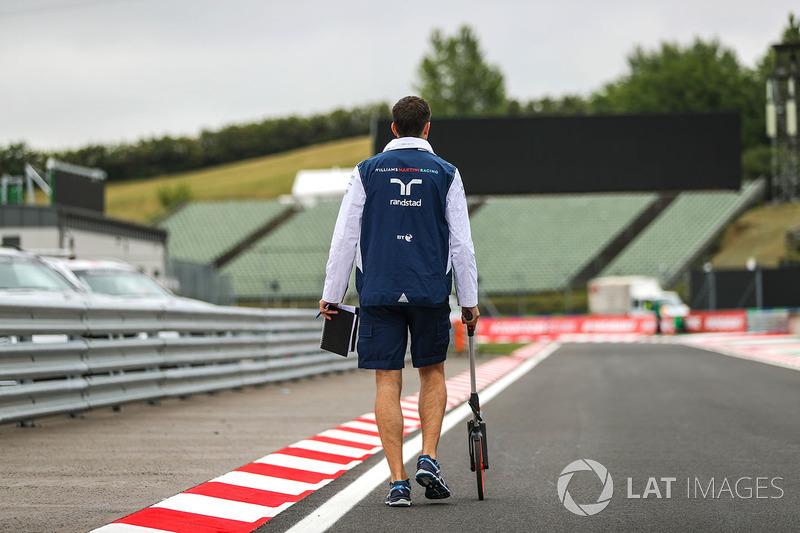 Mecánico de Williams camina la pista con una rueda de medición de distancia