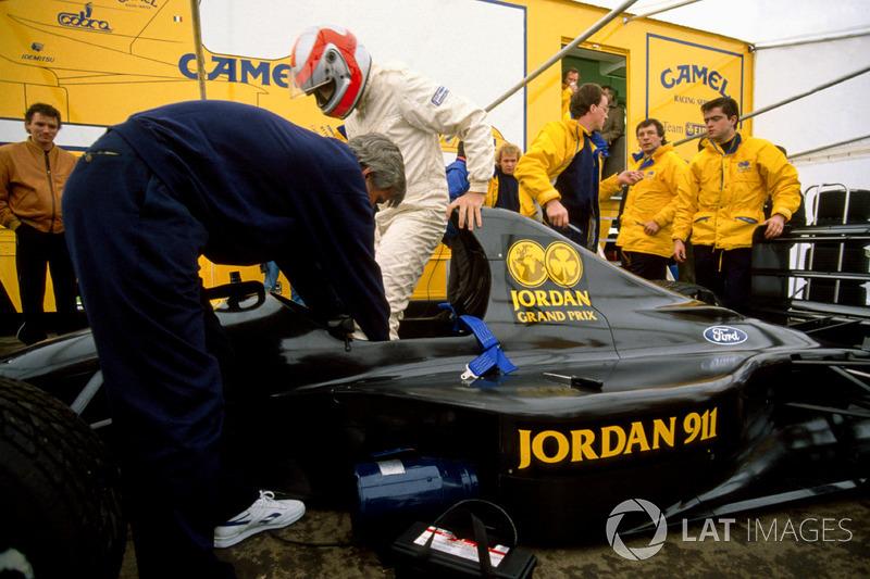 John Watson se monta en el nuevo Jordan 911 Ford con el diseñador Gary Anderson y Andy Stevenson en la foto (1990)