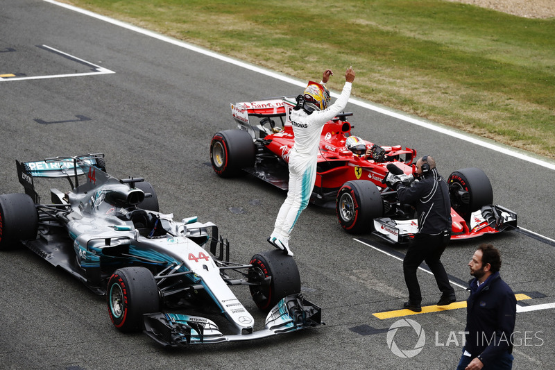 Lewis Hamilton, Mercedes AMG F1 W08, jumps off his car in celebration of pole position, alongside Sebastian Vettel, Ferrari
