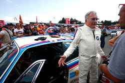 Veteran BMW racer Dieter Quester, talks to fans next to a BMW CSL