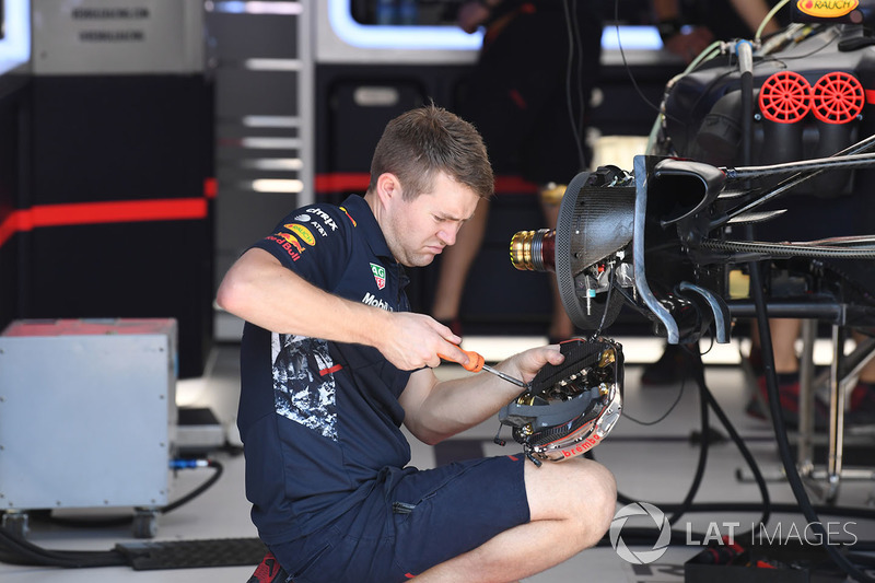Red Bull Racing mechanic works on Red Bull Racing RB13 front brake and wheel hub