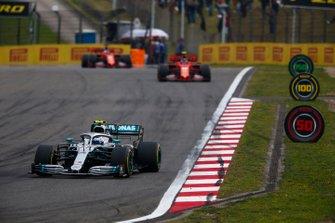 Valtteri Bottas, Mercedes AMG W10, leads Charles Leclerc, Ferrari SF90, and Sebastian Vettel, Ferrari SF90
