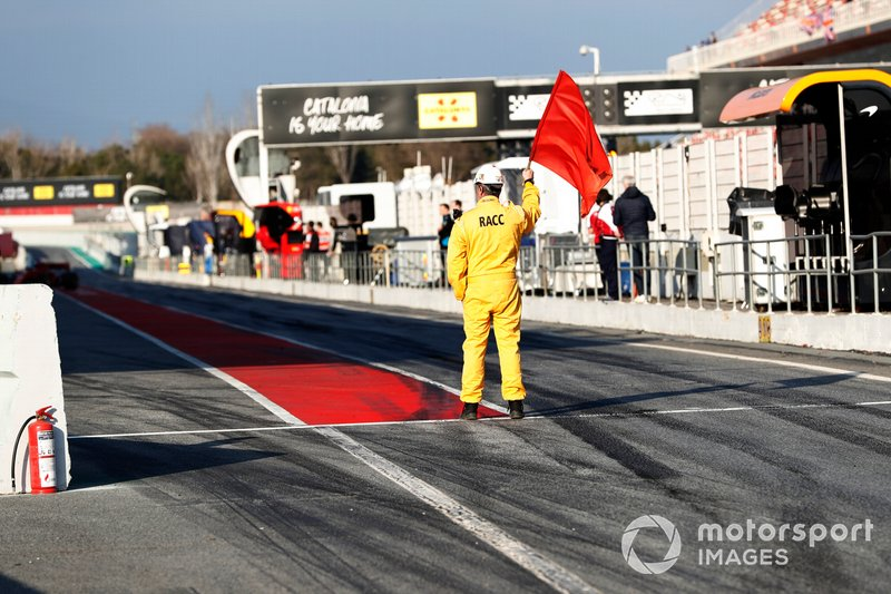 Un marshal sventola la bandiera rossa in pit lane
