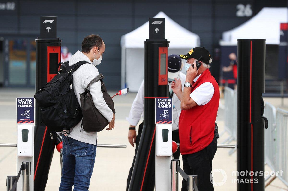 Robert Kubica, Alfa Romeo, muestra su pase a la entrada al paddock