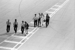 Bernie Ecclestone, Brabham Team Owner; Colin Chapman, Lotus Team Owner and James Hunt, McLaren, walk back