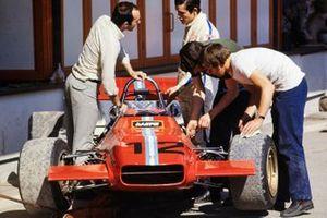 Jacky Ickx habla con Frank Williams mientras los mecánicos trabajan en el monoplaza de Piers Courage, De Tomaso 308 Ford
