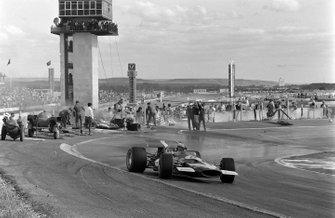 John Surtees, McLaren M7C Ford, slides through the corner as marshals work to extinguish a blazing car