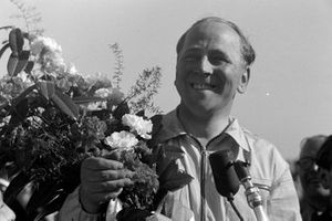 Reg Parnell receives a bouquet of flowers after finishing third