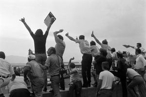 The Yardley British Racing Motors team celebrate on the pit wall as Jo Siffert claims victory
