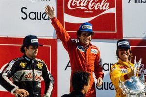 Alain Prost, 1st position, waves on the podium. Keke Rosberg, 2nd position, and Elio de Angelis, 3rd position, are on the podium