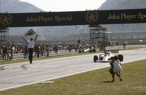 Alain Prost, McLaren MP4-2 TAG, takes the chequered flag