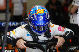 Fernando Alonso, McLaren, lowers himself into his seat