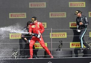 Charles Leclerc, Ferrari, 2nd position, and Lewis Hamilton, Mercedes, 1st position, celebrate on the podium with Champagne