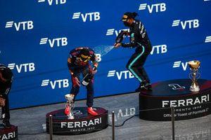 Lewis Hamilton, Mercedes, 1e positie, spuit Max Verstappen, Red Bull Racing, 2e positie, met Champagne op het podium