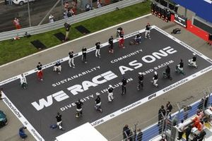 The drivers stand in support of the End Racism campaign prior to the start