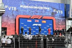 The Mercedes team delegate, Max Verstappen, Red Bull Racing, 2nd position, Lewis Hamilton, Mercedes, 1st position, and Carlos Sainz Jr., Ferrari, 3rd position, on the podium