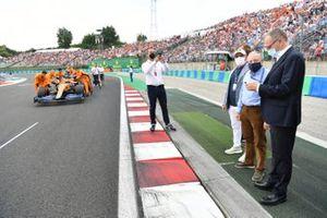 Jean Todt, presidente de la FIA, y Stefano Domenicali, director general de la Fórmula 1, junto a la parrilla mientras Daniel Ricciardo, McLaren MCL35M, llega con sus mecánicos
