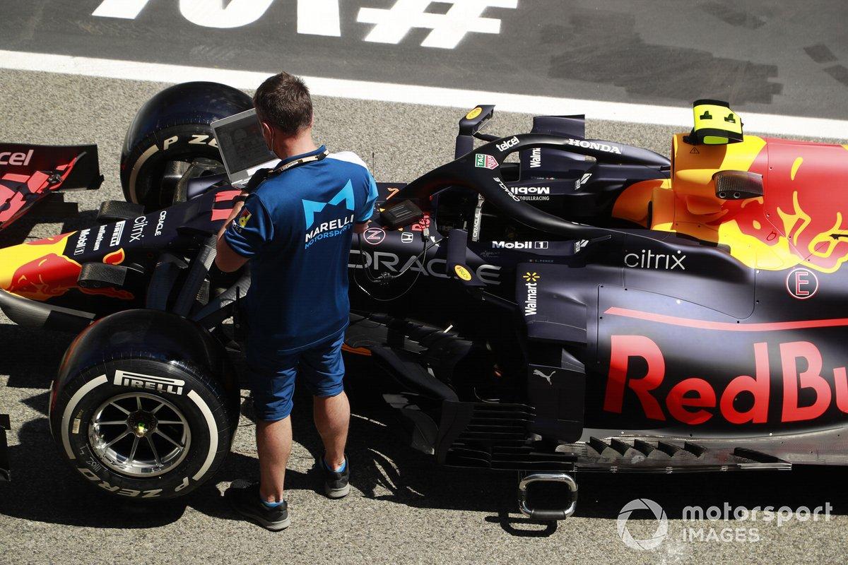 Un empleado de Marelli Motorsport trabaja en el Red Bull Racing RB16B de Sergio Pérez