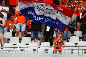 Fans of Max Verstappen, Red Bull Racing, cheer as the Dutch driver takes victory