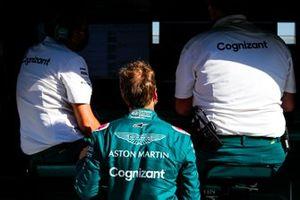 Sebastian Vettel, Aston Martin, talks to team mates on the pit wall