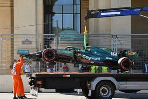 The car of Lance Stroll, Aston Martin AMR21, is lifted onto a flat-bed truck