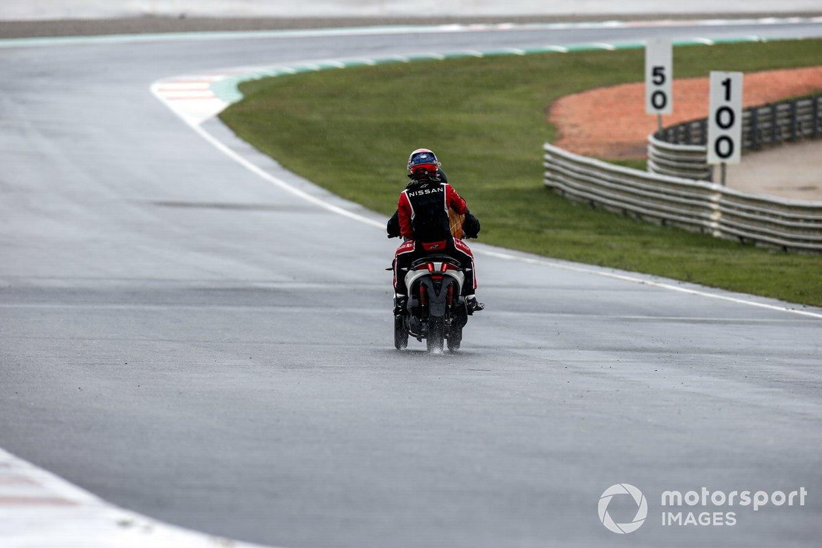 Sebastien Buemi, Nissan e.Dams en la parte trasera de un scooter después de retirarse de la carrera