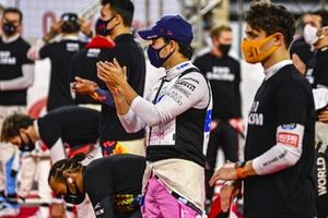 Sergio Perez, Racing Point, and the other driver stand and kneel in support of the End Racism campaign