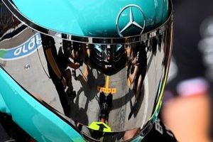 Mechanics reflected in the visor of a pit crew helmet