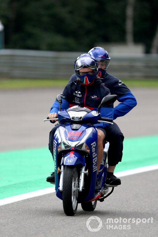 Toro Rosso team members ride on a scooter