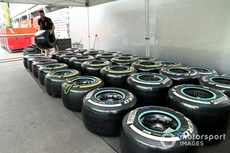 An AMG Mercedes F1 team member works on Pirelli tyres