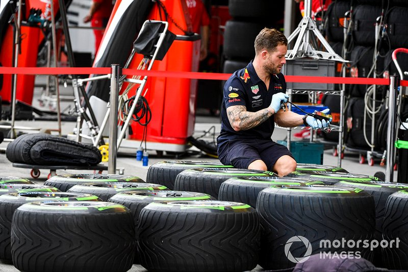 Un mécanicien Red Bull avec des pneus Pirelli