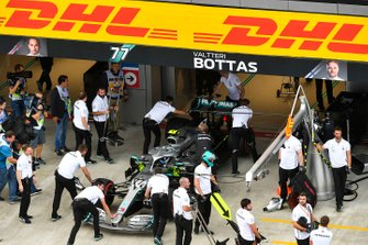 Valtteri Bottas, Mercedes AMG F1, is wheeled back into the team's pit garage