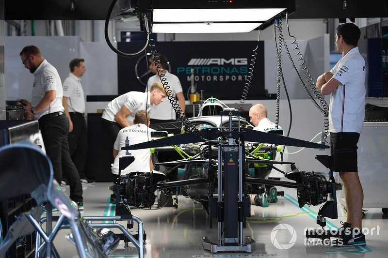 Mechanics work on the car of Lewis Hamilton, Mercedes AMG F1 W10, in the garage
