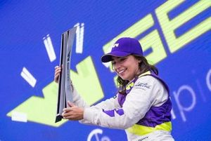 Jamie Chadwick celebrates on the podium with the trophy