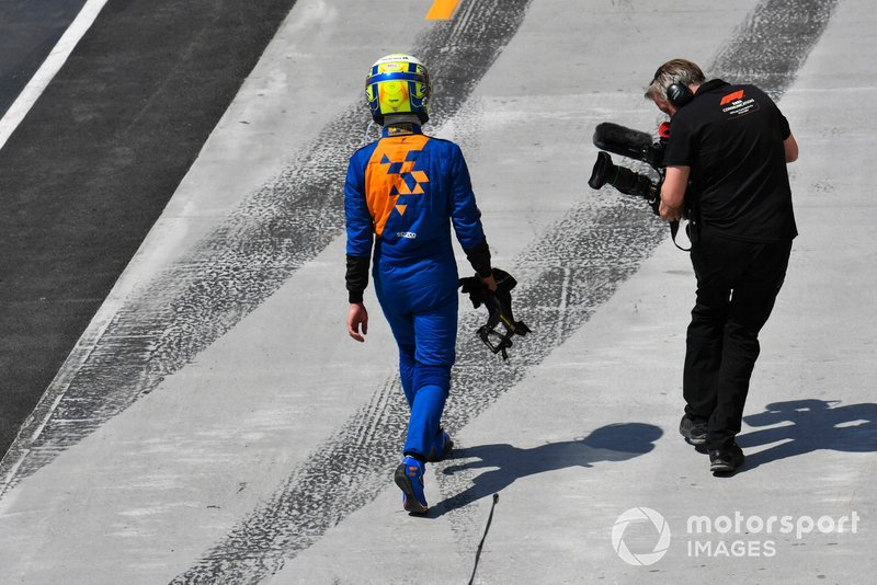 Lando Norris, McLaren, walks back to the garage after a failure ends his race