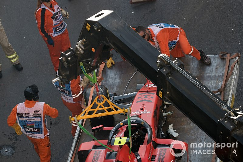 Los oficiales retiran el coche accidentado de Charles Leclerc, Ferrari SF90