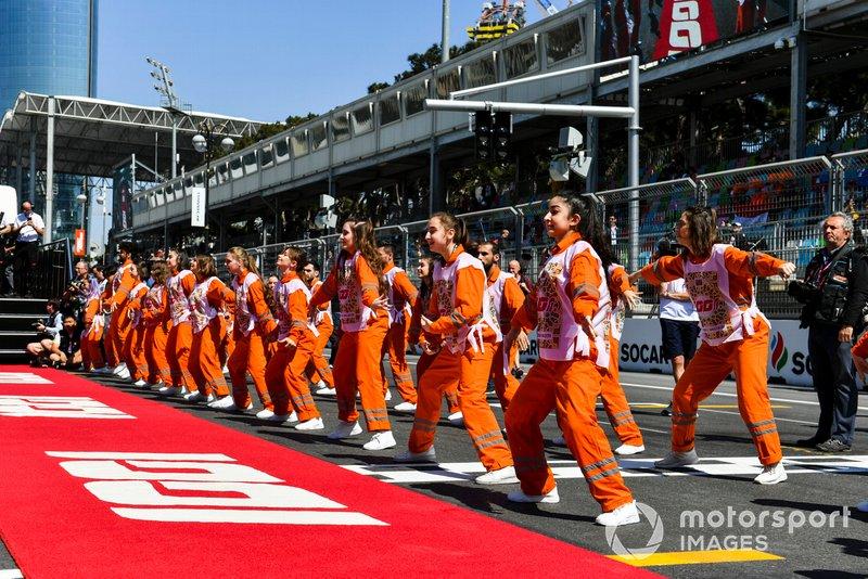 Oficiales de pista bailan antes de la carrera