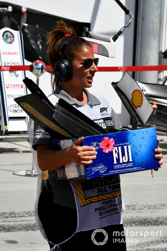 A marshal returns a box of bits from the damaged car of Kevin Magnussen, Haas VF-19, to the pits
