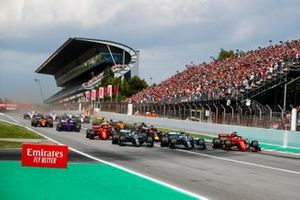 Lewis Hamilton, Mercedes AMG F1 W10, Valtteri Bottas, Mercedes AMG W10, and Sebastian Vettel, Ferrari SF90, battle for the lead as they lead the field towards the first corner at the start