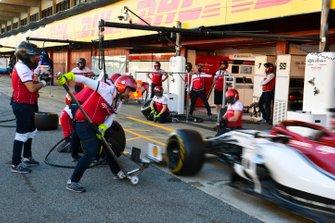 Un Alfa Romeo Racing C38 es atendido por mecánicos durante una parada en boxes de práctica.