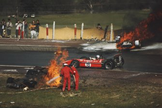Mario Andretti, March 701 Ford, passes the burning wreckage of the Jackie Oliver, BRM P153, and Jacky Ickx, Ferrari 312B, accident