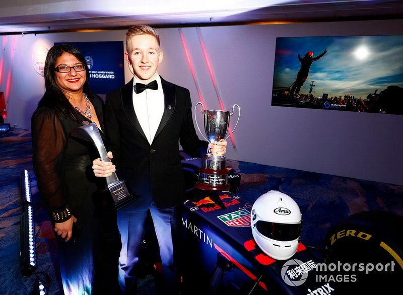 Il vincitore dell'Aston Martin Autosport BRDC Young Driver Award Johnathan Hoggard festeggia con gli amici e la famiglia con il trofeo e l'assegno vicino alla Red Bull Racing RB15
