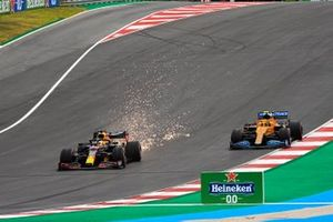 Sparks fly from the rear of Max Verstappen, Red Bull Racing RB16, as he battles with Lando Norris, McLaren MCL35