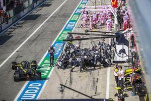 Esteban Ocon, Renault F1 Team R.S.20, sale de los boxes mientras Daniil Kvyat, AlphaTauri AT01, hace un pit stop