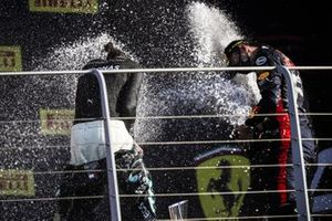 Lewis Hamilton, Mercedes-AMG F1, 1st position, and Alex Albon, Red Bull Racing, 3rd position, spray Champagne on the podium