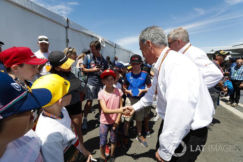 Chase Carey, presidente de la F1,y Ross Brawn, director de la FOM, se encuentran con los niños de la parrilla