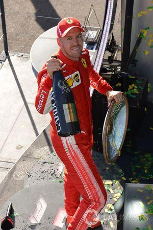 El ganador de la carrera, Sebastian Vettel, Ferrari, celebra ene l podio con el trofeo y champagne